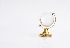 Genomskinligt jordklotobjekt med den guld- grunden royaltyfri foto