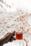 Genomskinligt råna med te Hand som rymmer en kopp te En råna av te hänger i luften i morgonen sammansättningen Royaltyfria Foton