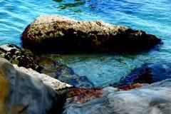 Genomskinligt vatten av Adriatiskt havet som tvättar några stenar royaltyfri foto