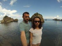 Genomsnittliga seende par på den steniga stranden Arkivbilder
