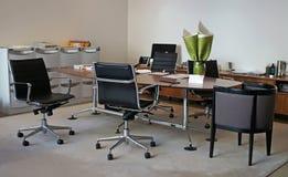 Genomsnittligt kontorsrum med konferenstabellen och enheter Arkivbilder