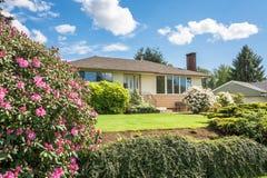 Genomsnittsfamiljhuset med rhododendron blommar framme Royaltyfri Bild