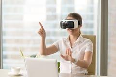 Genoten van jonge vrouw die VR-hoofdtelefoon met gebaren met behulp van stock foto's
