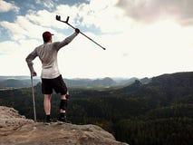 Genou de huttes de randonneur L'homme avec la jambe dedans joignent le séjour d'immobilisateur sur le sommet et soulèvent le crut Images stock