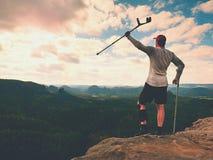 Genou de huttes de randonneur L'homme avec la jambe dedans joignent le séjour d'immobilisateur sur le sommet et soulèvent le crut Photo libre de droits