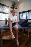 Genou se tenant patient masculin supérieur en douleur Photo libre de droits
