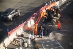 Workers dig hole in asphalt with excavator. Genova, Italy - January 18, 2018: Road works are in progress, workers dig hole in asphalt with orange excavator stock photography