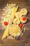 Genres de pâtes sèches avec des tomates-cerises sur un fond en bois brun Photo stock
