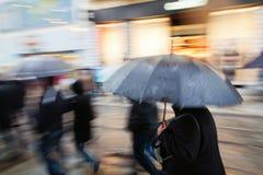 Gens d'achats marchant dans la ville pluvieuse photographie stock libre de droits