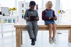 Gens d'affaires à l'aide des comprimés numériques tout en se reposant sur la table dans le bureau créatif Image stock