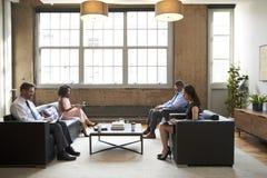 Gens d'affaires à l'aide des ordinateurs portables dans un salon rencontrant le secteur images libres de droits