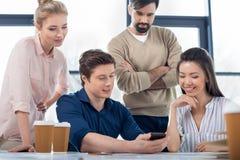Gens d'affaires à l'aide du smartphone sur la réunion de petite entreprise photographie stock libre de droits