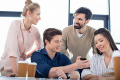 Gens d'affaires à l'aide du smartphone sur la réunion de petite entreprise photographie stock