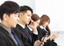 Gens d'affaires à l'aide et parlant du téléphone intelligent photos stock