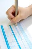 Gens d'affaires écrivant le stylo sur le borderau de versement Photographie stock libre de droits