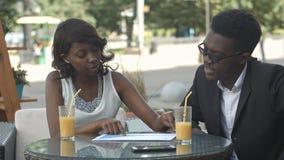 Gens d'affaires d'afro-américain tenant des articles, expliquant des détails tout en ayant une réunion à un café Photographie stock libre de droits