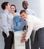 Gens d'affaires agissant l'un sur l'autre à un refroidisseur d'eau photo libre de droits
