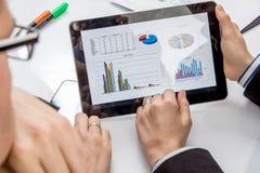 Gens d'affaires analysant des documents lors d'une réunion Photo stock
