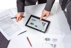 Gens d'affaires analysant des documents lors d'une réunion Image stock