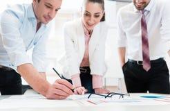 Gens d'affaires analysant les données - verres sur le graphique Images stock
