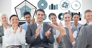 Gens d'affaires applaudissant avec des graphiques à l'arrière-plan Photographie stock