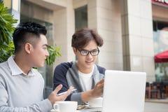 Gens d'affaires asiatiques avec le costume occasionnel fonctionnant dans le café Image libre de droits