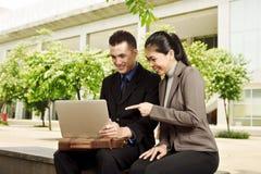 Gens d'affaires asiatiques discutant le travail avec l'ordinateur portable Images stock