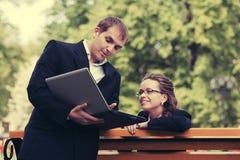 Gens d'affaires avec l'ordinateur portable en parc de ville Photographie stock
