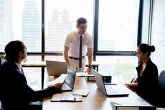 Gens d'affaires avec le chef discutant ensemble dans la salle de conférence au cours de la réunion au bureau Images libres de droits