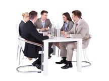 Gens d'affaires ayant la conférence se réunissant au-dessus du fond blanc Image stock