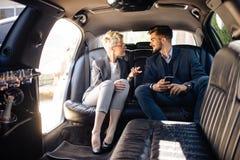 Gens d'affaires ayant le disccusion dans la limousine Photos stock
