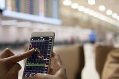 Gens d'affaires commerçant la bourse des valeurs de forex sur le mobile à l'airpor images stock