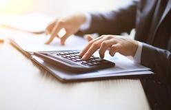 Gens d'affaires comptant sur la calculatrice reposant la table Fermez-vous des mains et de la papeterie Image libre de droits