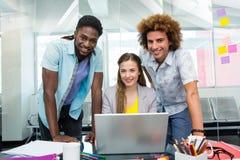 Gens d'affaires créatifs à l'aide de l'ordinateur portable au bureau Photos stock