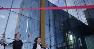 Gens d'affaires croisant la ligne d'arrivée banque de vidéos