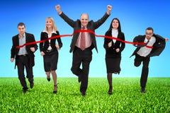 Gens d'affaires croisant la ligne d'arrivée Photographie stock libre de droits