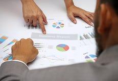 Gens d'affaires d'équipe d'analyste pendant la discussion de l'examen financier, doigt de point au document de graphique, après P Photos libres de droits