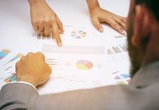Gens d'affaires d'équipe d'analyste pendant la discussion de l'examen financier, doigt de point au document de graphique, après P Photo stock