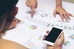 Gens d'affaires d'équipe d'analyste pendant la discussion de l'examen financier, doigt de point au document de graphique, après P Photos stock