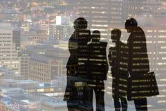 Gens d'affaires de silhouettes contre la ville Photos stock