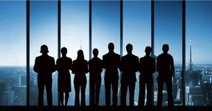 Gens d'affaires de silhouettes contre le bâtiment Photo stock