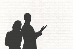 Gens d'affaires de silhouettes contre le mur blanc Images stock