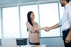 Gens d'affaires de sourire se serrant la main au cours de la réunion au bureau Images libres de droits