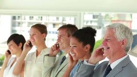 Gens d'affaires de tous les âges souriant au téléphone banque de vidéos
