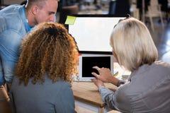Gens d'affaires discutant au-dessus du comprimé numérique Photo stock