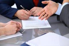 Gens d'affaires discutant le contrat Fermez-vous de la main masculine indiquant le papier Images stock