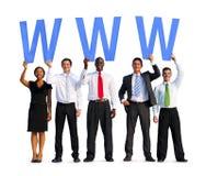 Gens d'affaires divers tenant les lettres WWW image stock
