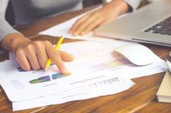 Gens d'affaires employant des finances d'ordinateur portable et de rapport pour se réunir Image stock