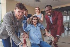 Gens d'affaires enthousiastes réussis de groupe d'équipe de collègue de poussée s'asseyant dans la chaise Images libres de droits