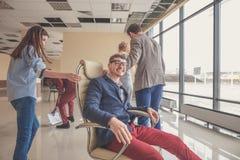 Gens d'affaires enthousiastes réussis de groupe d'équipe de collègue de poussée s'asseyant dans la chaise Photos stock